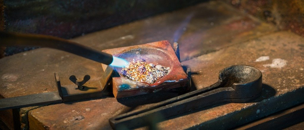 goldsmith-melting-gold-and-silver-granules-in-a-crucible-with-a-gas-picture-id1028699412